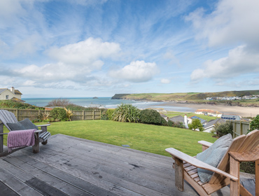 Fantastic, far reaching sea views across the decking and garden towards Pentire Point from self catering holiday house Sandrock.