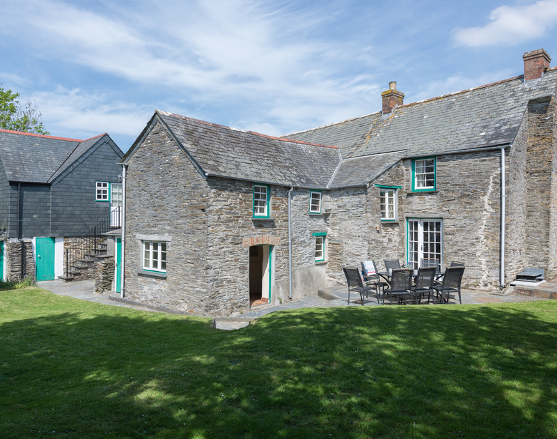 The rear exterior view of stone and slate clad Porthilly Greys with its terrace and separate annexe