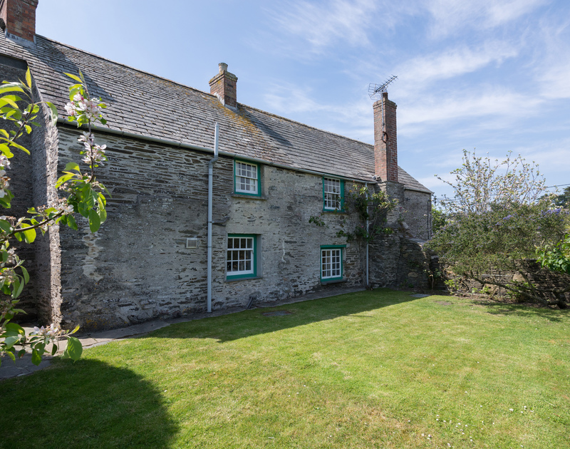 The stone clad exterior and lawned garden of Porthilly Greys, a traditional holiday cottage to rent