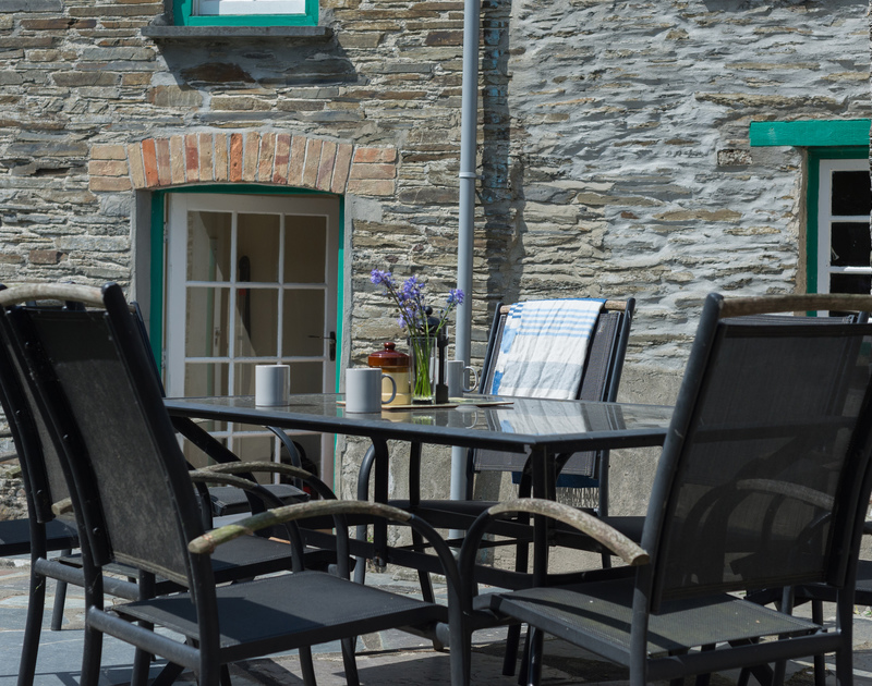 Sip a coffee at the table on the paved terrace of Porthilly Greys, a traditional holiday house in Rock