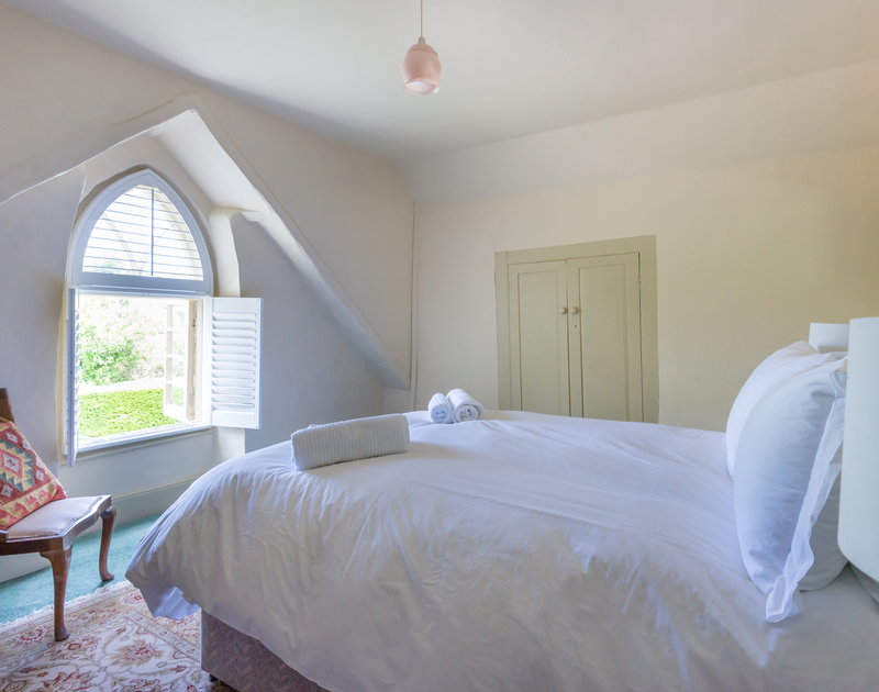 A double bedroom at Porthilly Greys, with attractive arched window.