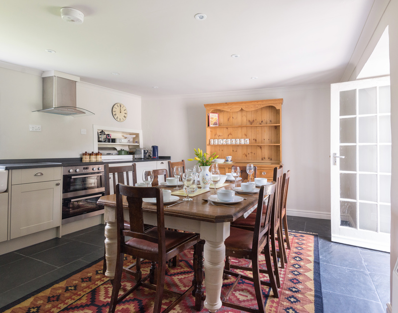 A large dining table next to the kitchen stove and worktops with doors to garden.