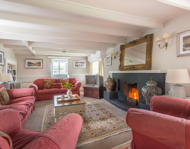 Elegant sitting room with characterful ceiling beams and open fire at Porthilly Greys
