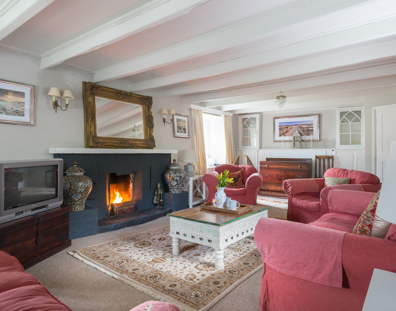 The sitting room with open fire at Porthilly Greys, a holiday rental in Rock
