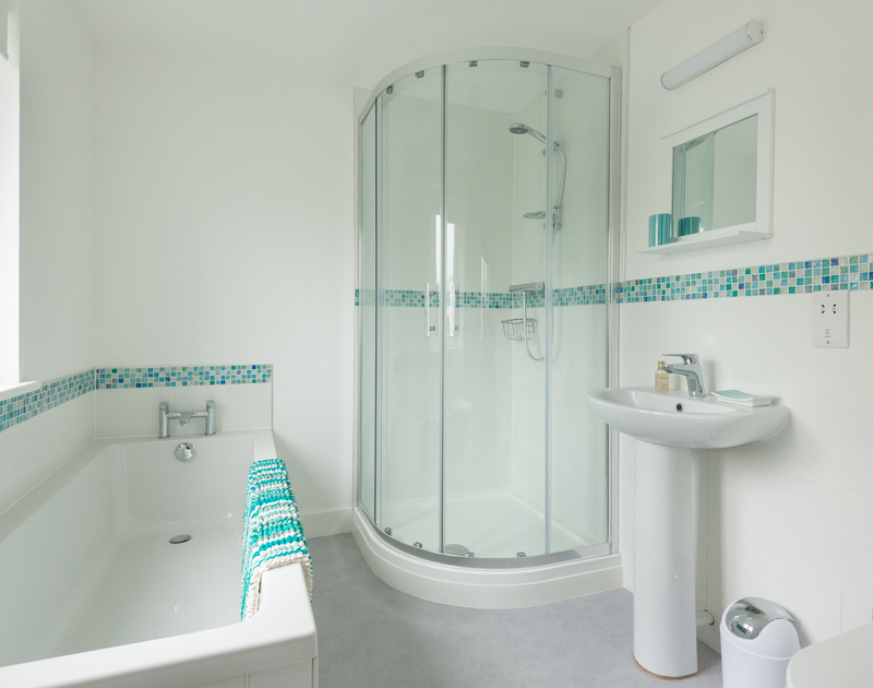 The ensuite bathroom with shower, W.C. and hand basin at Pendragon House, Port Isaac.