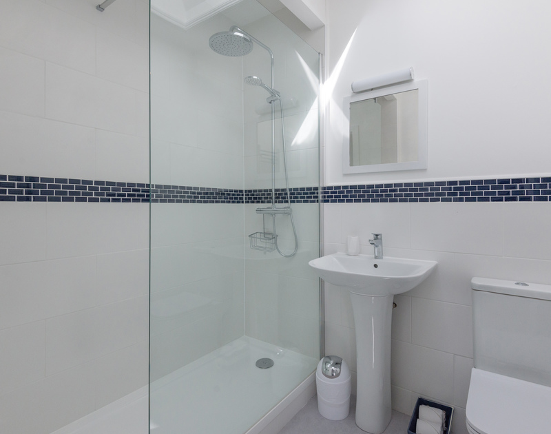 The large shower in the smart blue and white ensuite shower room with W.C and hand basin at Pendragon.