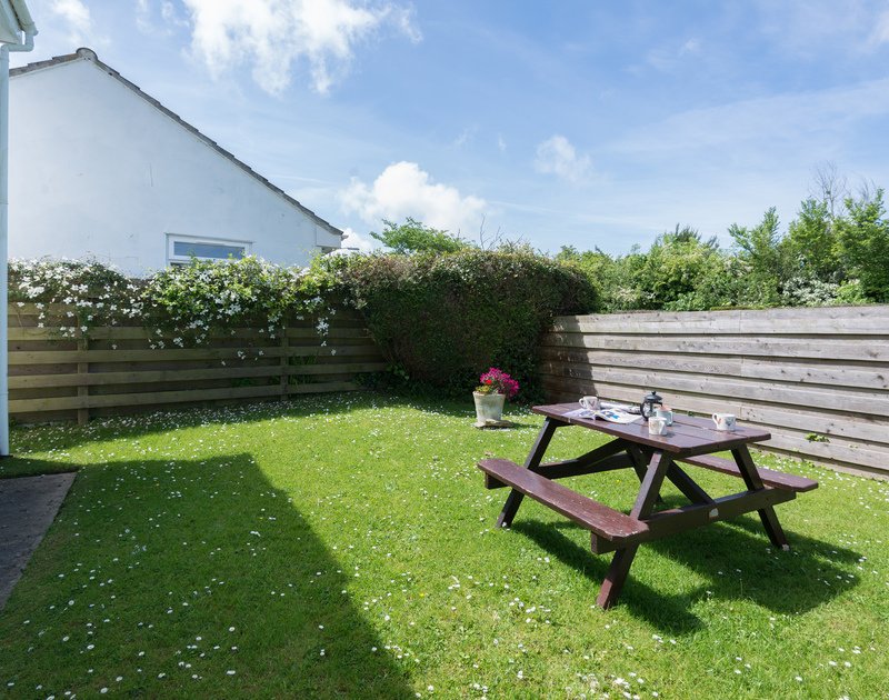 The rear lawned garden of Hazlehurst, self-catering holiday accommodation, with its picnic bench and sunny aspect