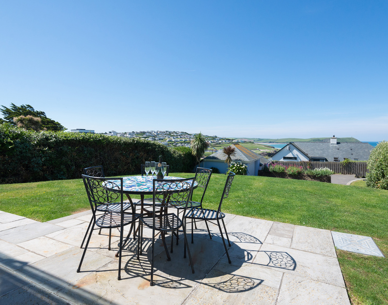 The sunny terrace at Bryher, a stunning self-catering holiday house in Polzeath, Cornwall, with table and chairs.