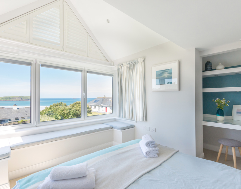 The master double bedroom at Bryher, a superb holiday house in Polzeath, Cornwall, offers stunning views with a door to the terrace.