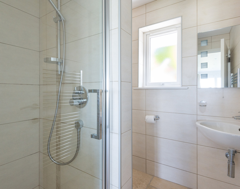 The double ensuite at Bryher, it's contemporary style shower room with large tiles throughout