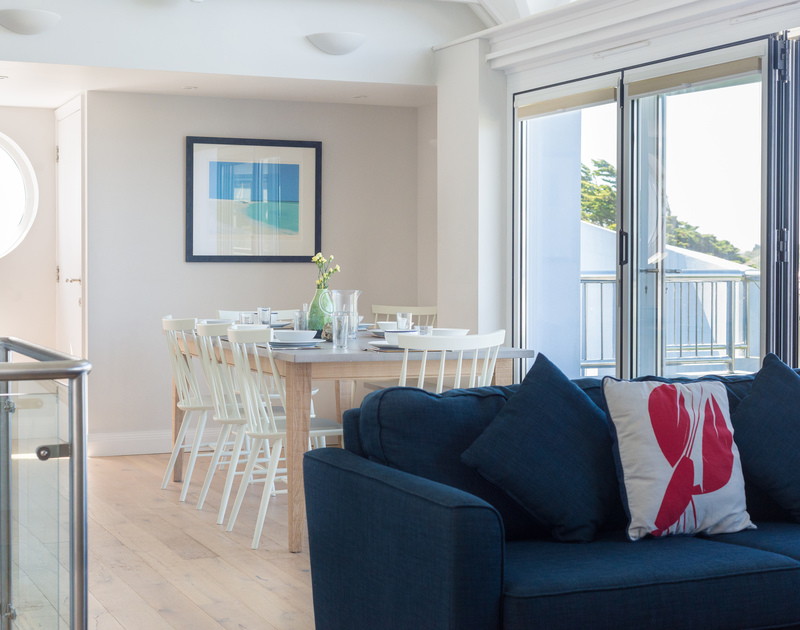 Open-plan, reverse-level living at Bryher with the dining table opening onto the balcony