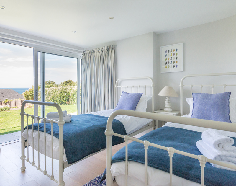 Ground-floor twin bedroom at Bryher, a holiday house in Polzeath, Cornwall, with doors to the garden.