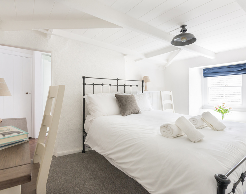 The double bedroom at holiday rental Bre Cottage, in Port Isaac, wth attractive bedsteads.