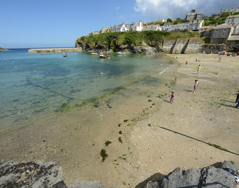 Children playing on the beach at high tide in Port Isaac