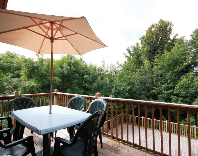 The balcony with table and chairs in the sun, perfect for lunch and evening bar be ques, stairs down to the large lower deck area, at Owls rest a self catering house in Rock, Cornwall