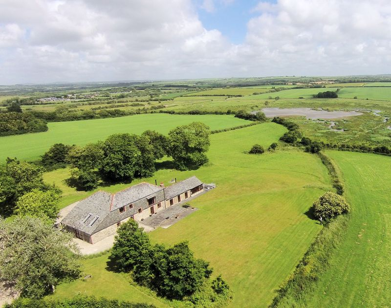 An aerial view showing the gardens of The Mill barn, an attractive barn conversion in a glorious rural setting for self catering holidays in Lower Amble near Rock, Cornwall.