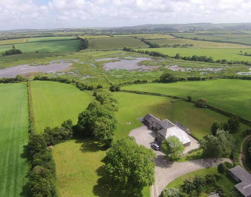 An aerial view of The Mill barn, an attractive barn conversion in a glorious rural setting with wet land bird sanctuary in the distance, available to rent for self catering holidays in Lower Amble near Rock, Cornwall.