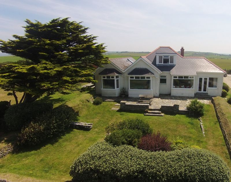 A drones view of the front of Tresawl, a self catering holiday house to rent, set in a stunning position above the cove at Epphaven near Polzeath in North Cornwall.
