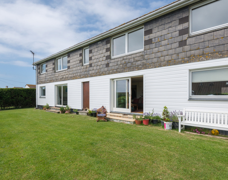 The communal gardens and the exterior of Polzeath Court with holiday apartment number 1 with its sliding glass doors open.