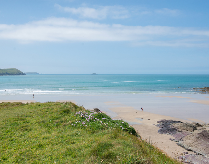 The large surfing mecca of Polzeath Beach with Stepper Point and Newlands island beyond, just a short walk downhill from self catering holiday apartment Polzeath Court 1.