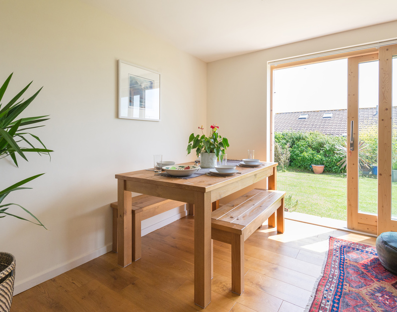 The dining table in the light of the large glass doors off the living room at south facing holiday apartment Polzeath Court 1 in North Cornwall.