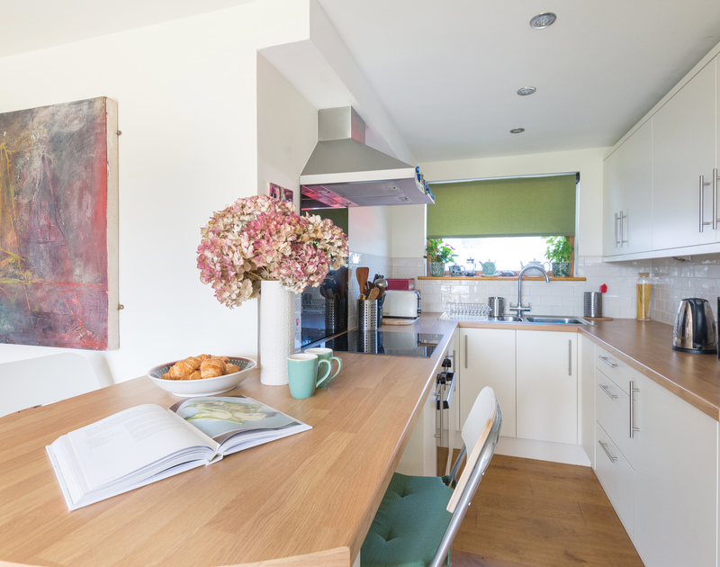 The neat compact, kitchen with breakfast bar in the open plan living area of Polzeath Court .