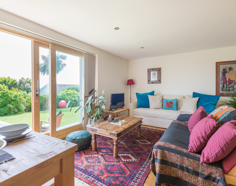 The colourful and comfortable living room at Polzeath Court 1, a self catering, holiday rental in walking distance of Polzeath Beach in North Cornwall.