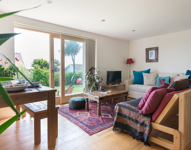Sliding glass doors introduce light into the living room at Polzeath Court 1, a self catering holiday home to rent.