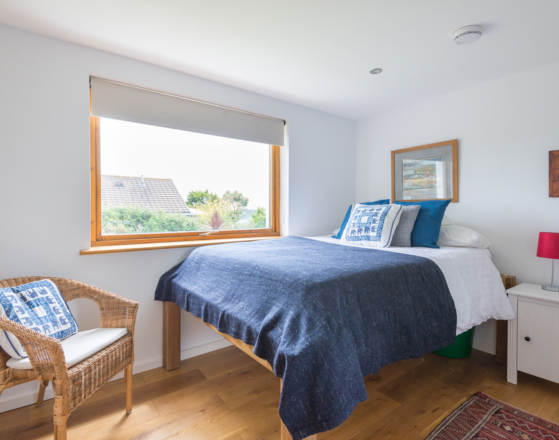 The double bedroom with a good sized window overlooking the garden at Polzeath Court 1, a self catering holiday apartment to rent on the North Coast of Cornwall.