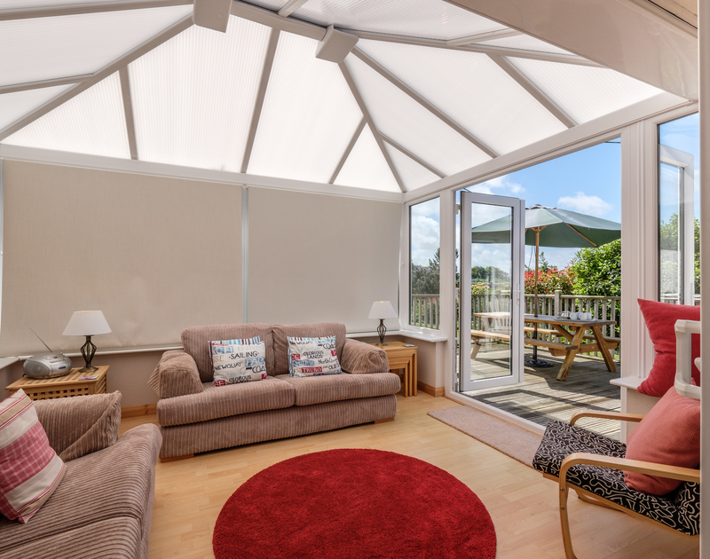 Curl up with a good book in the light and spacious conservatory at Cogenhoe, a holiday cottage to let with John Bray Cornish Holidays