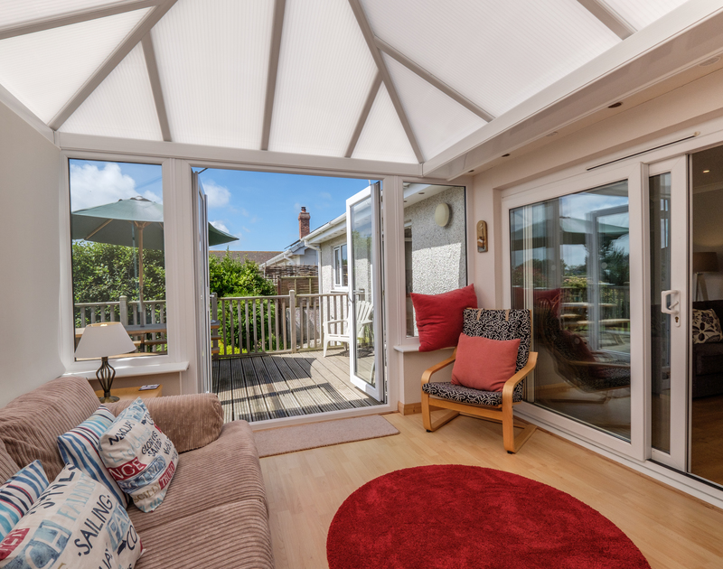 The spacious and welcoming conservatory at Cogenhoe, is a comfortable spot from which to enjoy the garden.