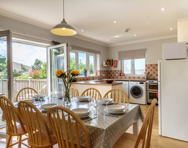 Throw open the patio doors and let the fresh Cornish air in as you dine in the bright open plan kitchen/dining room in Cogenhoe, a self catering holiday home in Rock, North Cornwall.