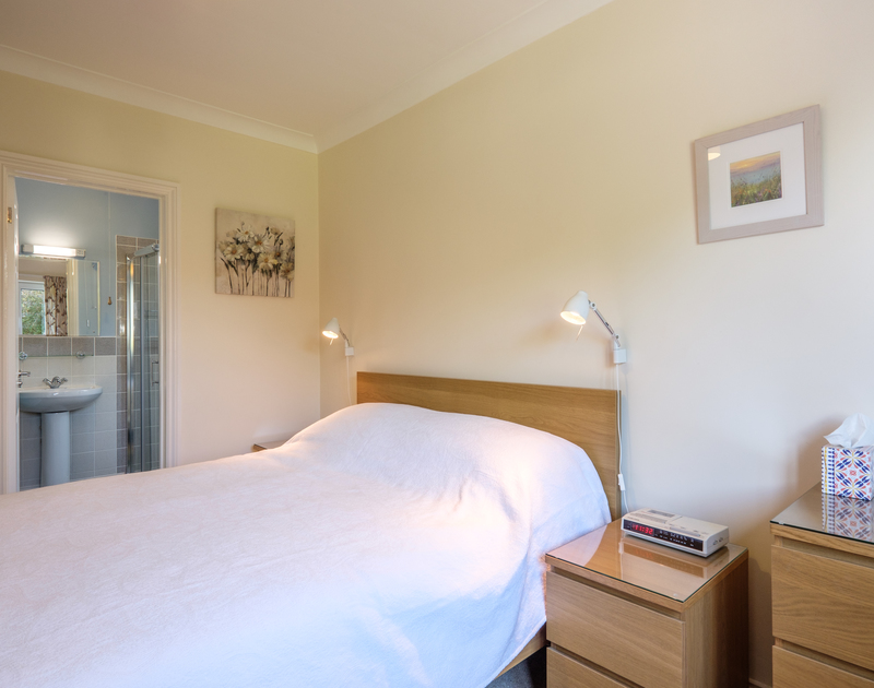The comfortable master bedroom at Cogenhoe a self catering holiday cottage in Rock, Cornwall has an ensuite shower room