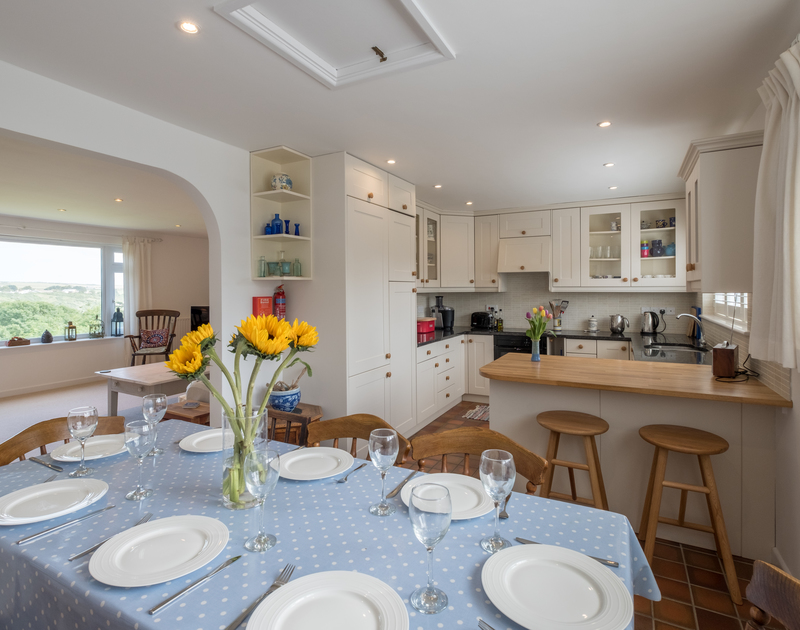 Semi open plan kitchen/diner and sitting room on the upper ground floor level at self catering holiday home Trestar, in Polzeath, North Cornwall.