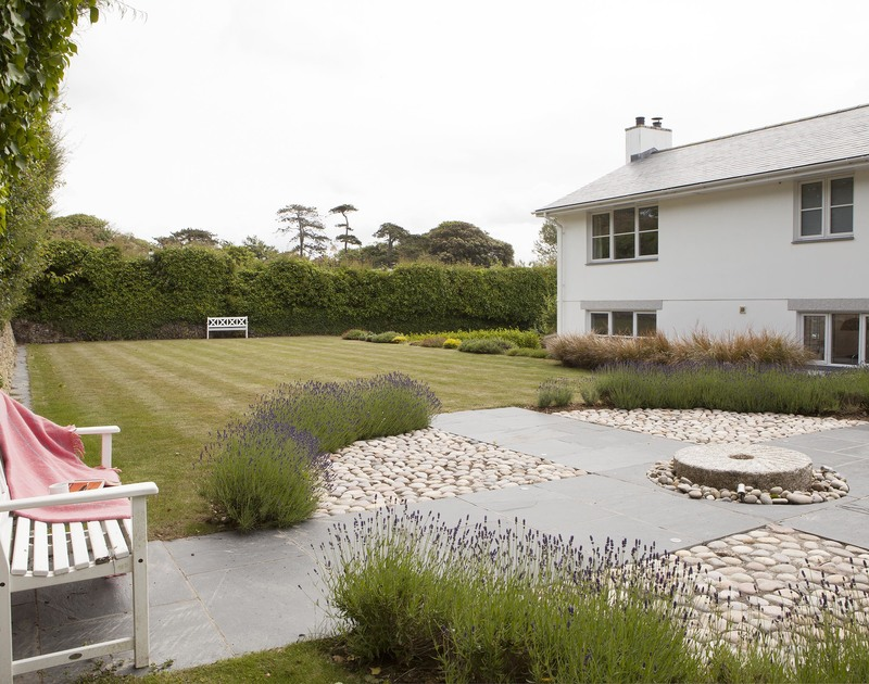 The sheltered rear lawned garden and the pretty paved terrace at Cherrytrees, a self catering holiday house to rent in Rock, North Cornwall.