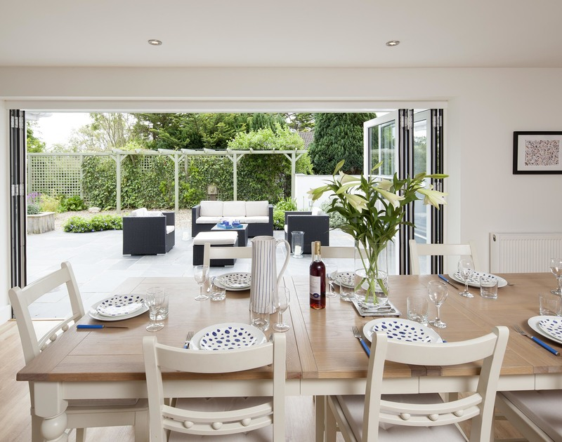 The spacious, light filled dining room with wide bi-fold doors to the garden at Cherrytrees, a self catering holiday house close to the Camel Estuary in Rock, North Cornwall.