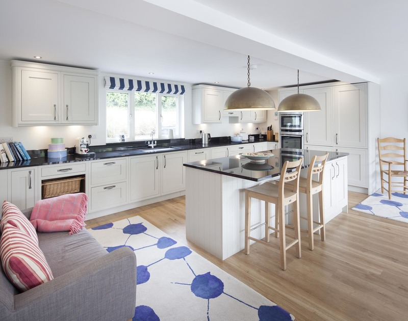 Light spills into the contemporary open plan kitchen in Cherrytrees, Rock, which has a breakfast bar and sofa and adjoins the cosy living room