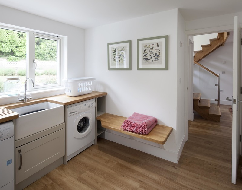 Large belfast sink and white goods in the utility room at self catering, holiday house Cherrytrees in Rock, North Cornwall.