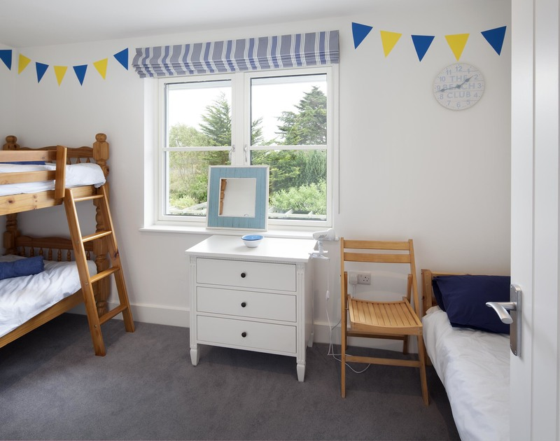 Colourful childrens bedroom at Cherrytrees with a set of bunkbeds and a single bedstead.