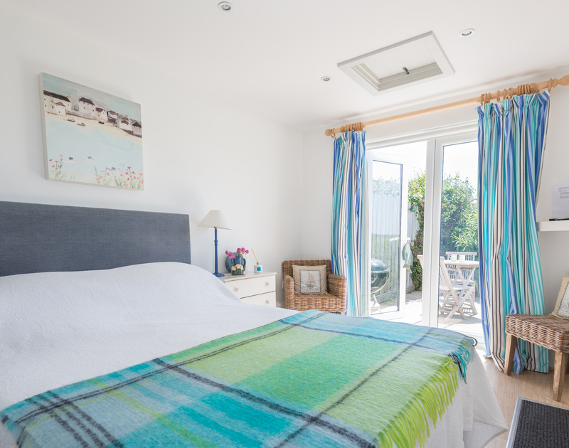 Double bedroom at The Point, a self-catering holiday house at Polzeath, Cornwall, with french windows to the garden.