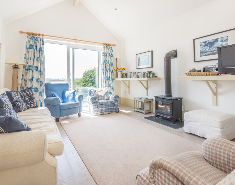 The comfortable, elegant sitting room at The Point, a coastal holiday house at Polzeath, Cornwall, with gas stove.