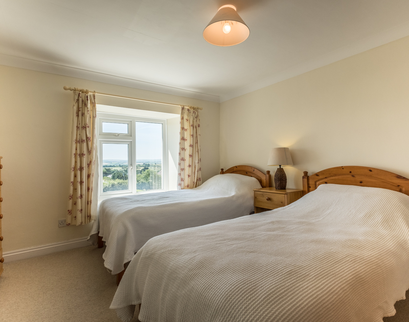 One of two pretty twin bedrooms in Trewint Farmhouse, a self catering holiday rental near Daymer Bay in  Cornwall.