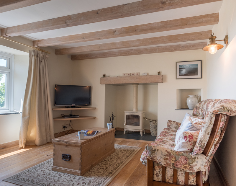 The lounge with wood burner at Trewint Farmhouse, a self catering holiday house to rent in Trebetherick, Daymer Cornwall.