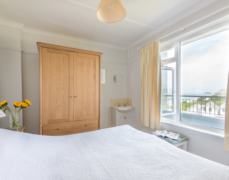 The master bedroom at Treverbyn, a holiday house in Polzeath, Cornwall, with king size bed and large mirrored wardrobe.