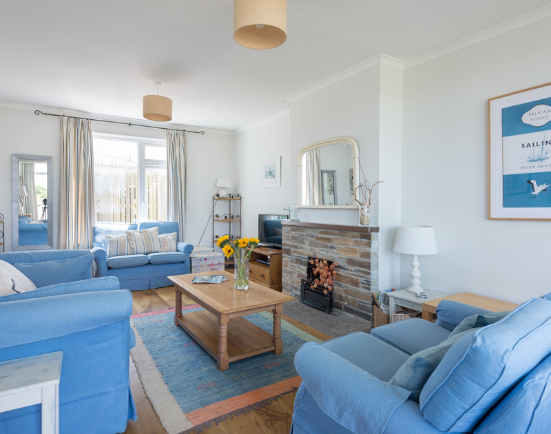 Attractive, comfy sitting room of Treverbyn, a holiday rental in Polzeath, Cornwall, with its open fire place.