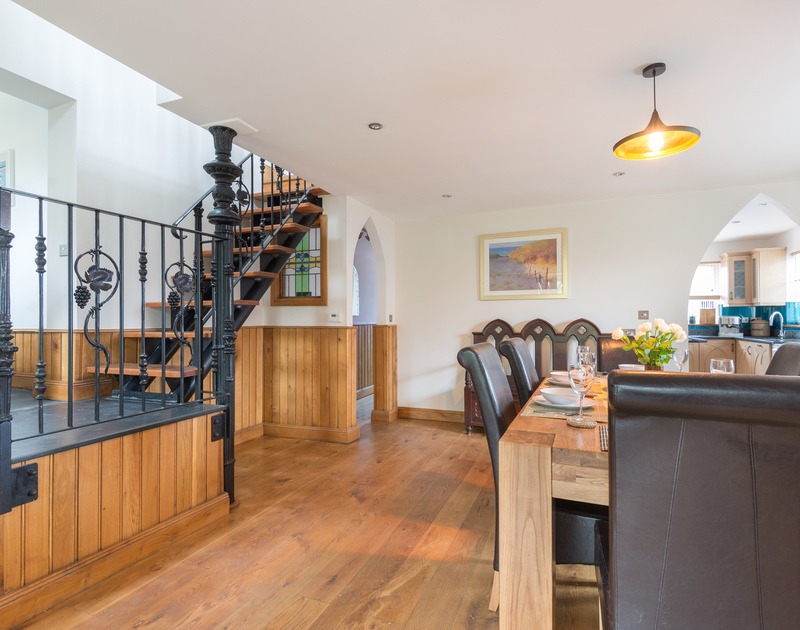 The elegant dining room with warm wooden flooring and an open tread, wrought iron staircase at self catering holiday house Fairholme, five minutes walk from the picturesque harbour in Port Isaac.