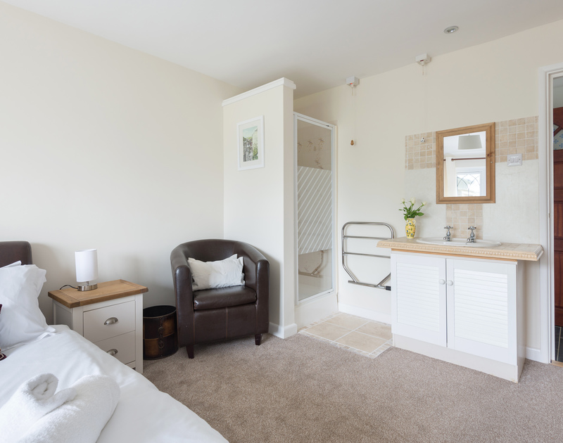 The shower cubicle, towel rail and hand basin in the ground floor double bedroom at self catering holiday house Fairholme in Port Isaac in North Cornwall.