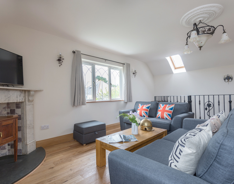 The sitting room at Fairholme has sea and coastline views from the elevated location of this self catering holiday house only a five minute walk away from the pretty harbourside in Port Isaac.
