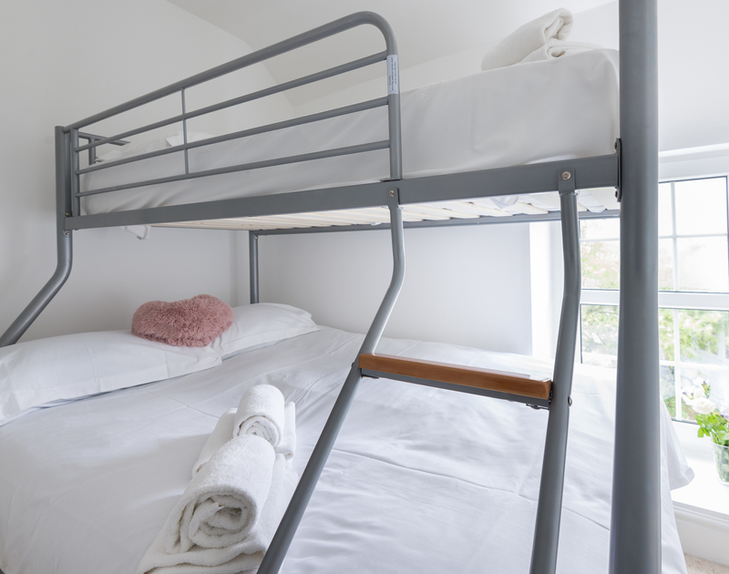 The triple bunk bedroom with a double bed on the lower bunk and a single above at Beehive Cottage, self catering holiday accommodation with terrific views over Lobber Point on the North Coast of Cornwall in Port Isaac.