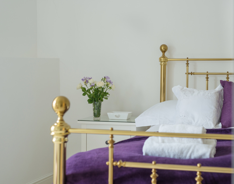 Relax in the gold framed king size bed in the master bedroom at Beehive Cottage, a self catering holiday home to rent in Port Isaac in Cornwall.